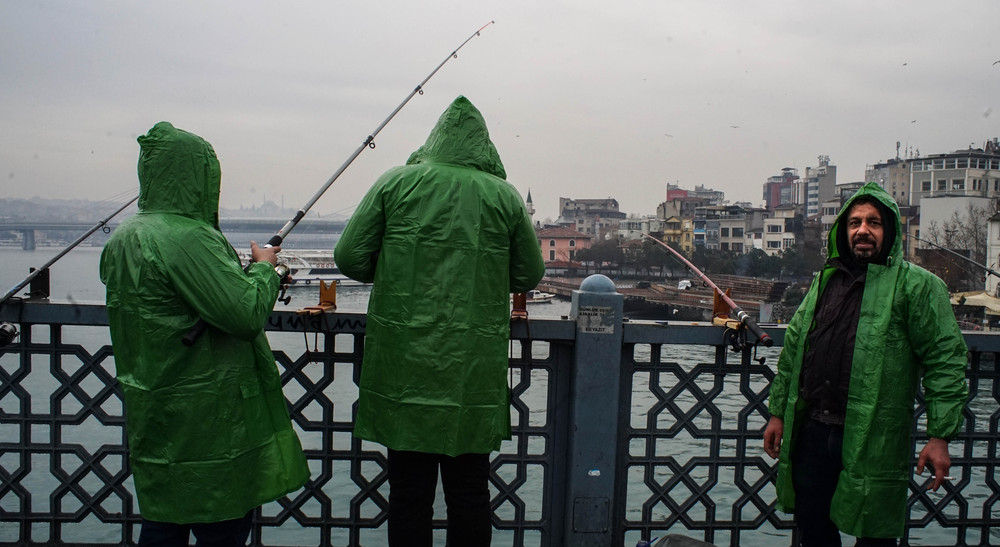 Three fishermen fishing from Galata Bridge in Istanbul.