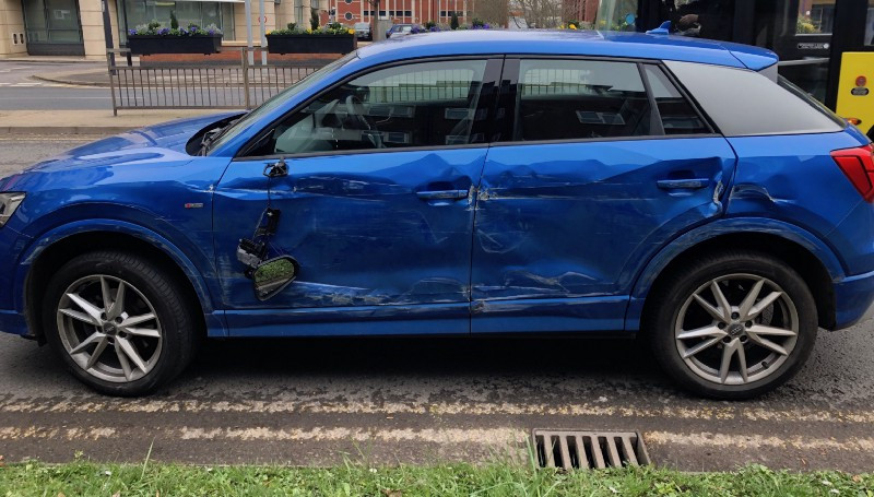 A blue Audi SUV with crash damage
