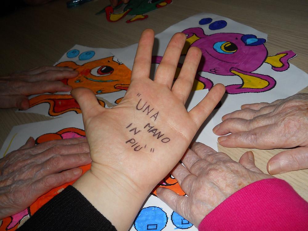 """Una mano aperta con palmo verso l'alto e su scritto a penna """"una mano in più"""" che è il nome del progetto del servizio civile proposto da AICCOS"""