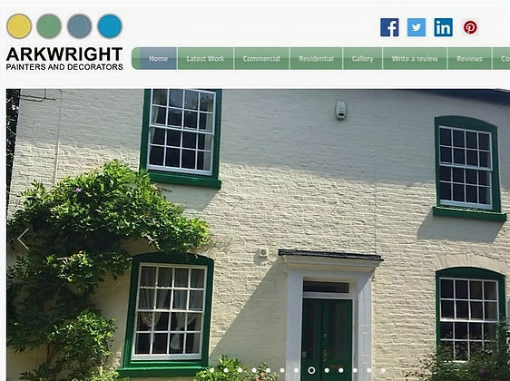 Whitewashed cottage with green sash windows and door