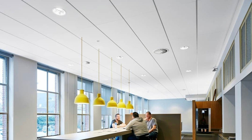 men sitting at a table under shiny yellow pendant lights hanging from suspended ceiling in Derby