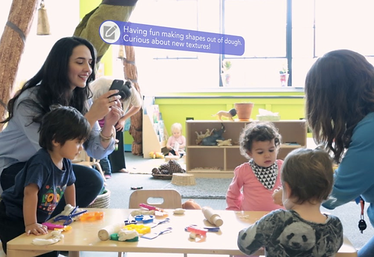 Photo of teachers playing with and interacting with children in their classroom. Teachers are using the free brightwheel app to send updates to parents throughout the day.