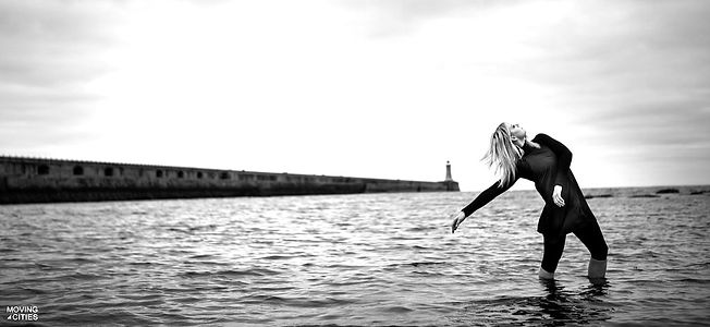 This image is from our Moving Cities North East exhibition. The dancer is Katherine Whale and she is dancing in the sea at North Shields where the pier can be seen in the background and she is reaching in a backbend towards the sea water behind her. She is wear dark clothing and her blonde hair is blowing in the wind.