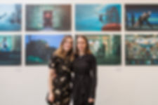 The image shows Rachel and Hannah smiling with their arms around each other. Rachel is wearing a plain black dress and Hannah has a black dress with a cream flower pattern. In the background on the wall is their Moving Cities North East exhibition prints, showing dancers performing in locations across the North East.