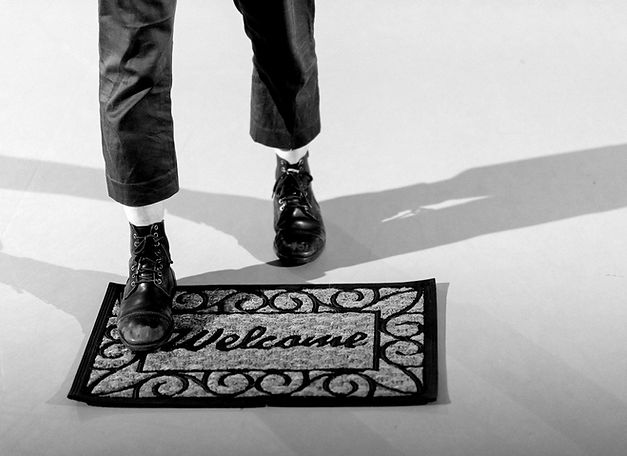 This image is of a dancers feet. She is wearing heavy leather lace up boots and cropped trousers. She is stepping forward onto a doormat which has Welcome written on it. The image is intentionally faded as it's the background to the title text.
