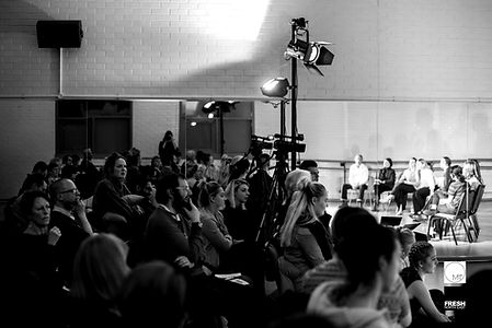 This image is a wide shot of the studio, audience and performers at one of our fresh north east scratch platforms. On the left and centre we can see a big audience seated together, on the right we can see a semi circle of artists sitting facing the audience. There is also a lighting rig in the centre of the image.