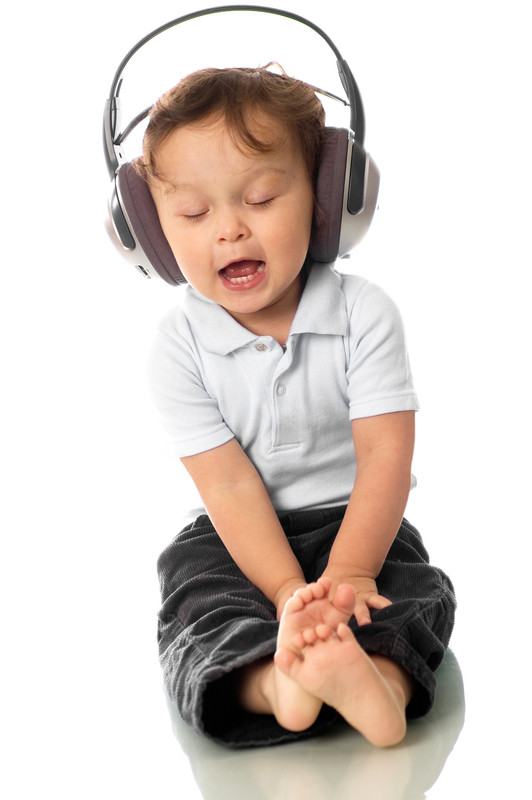 Funny photo of toddler sitting with eyes closed and mouth open singing enjoying listening to music in large adult-size headphones.