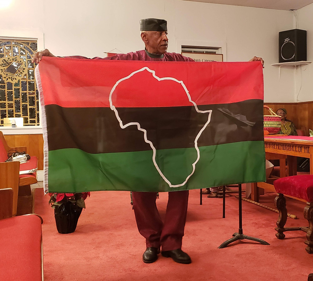 Jimmy O. White holds up the red, black, and green flag to share the symbols of Kwanzaa