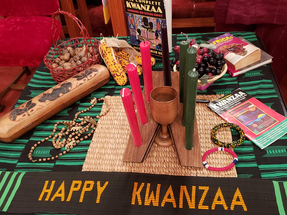 Symbols of Kwanzaa displayed on a table, including the Kinara with red, black, and green candles.