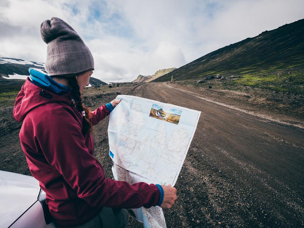 Femme consulte carte et itinéraire en Islande pour Le meilleur voyage en voiture en Islande