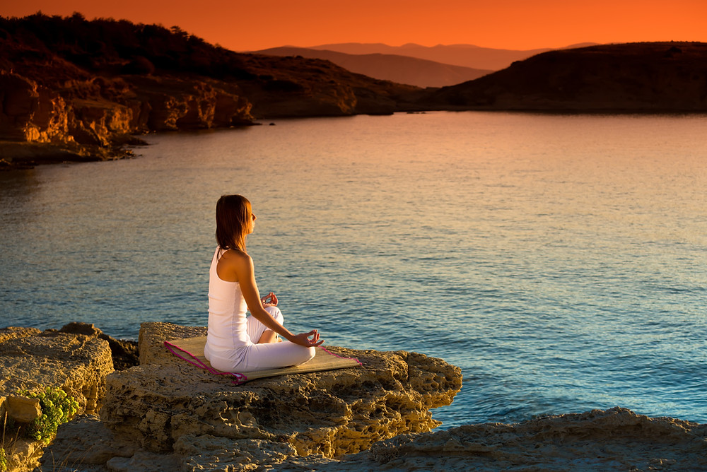 Woman wearing white doing yoga on a rock that juts out into a tranquil body of water.