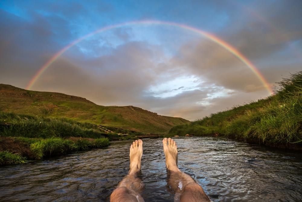 Baignade dans une source d'eau chaude de Reykjadalur et arc-en-ciel- Sources thermales d'Islande