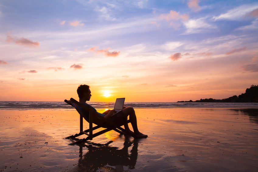 Silhouette of a man sitting in a folding chair on a tranquil beach as the sun sets behind him.