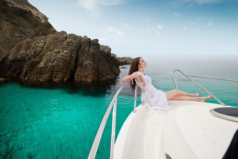 Relaxed woman in white dress sitting on the front of a white boat in bright, green water