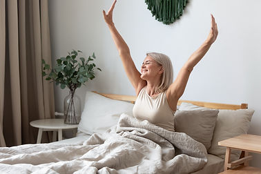 Happy fresh mature middle aged woman stretching in bed waking up alone happy concept, smil