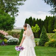 Bride back of dress purple flowers green lawn