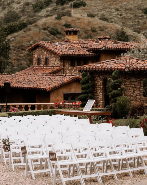 wedding ceremony with white resin padded chairs