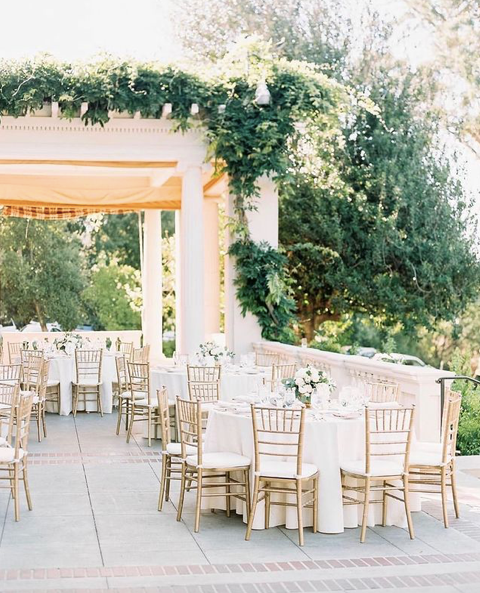 outdoor wedding reception with gold chiavari chairs