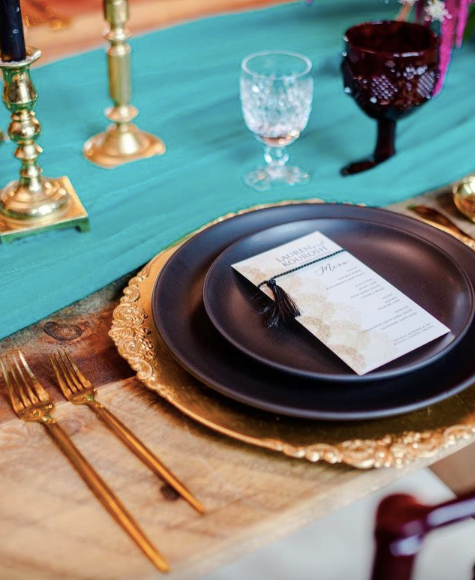 black dinner plates with gold accents on a wedding reception table