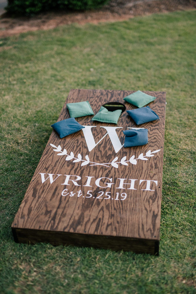 outdoor wedding reception with lawn games featuring corn hole