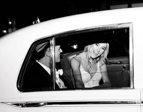 black and white photo of a bride and groom in their getaway car leaving their wedding