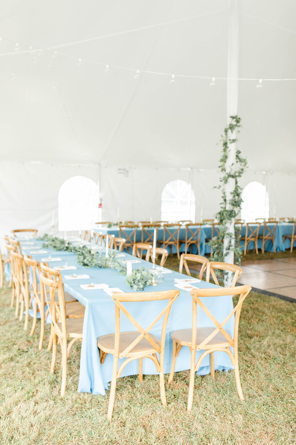 tent wedding with cross back chairs, blue tablecloths and garland