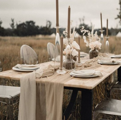 outdoor wedding reception with wood tables, beige table runners, ghost chairs, and tan candlesticks