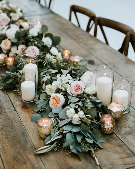 eucalyptus garland with peach flowers and candles in hurricane vases