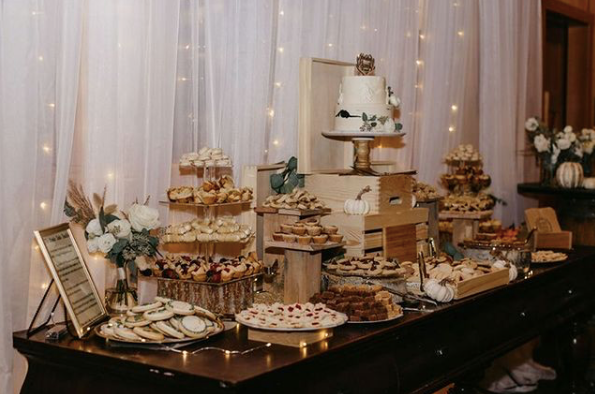dessert bar at wedding with cake, cookies and cupcakes