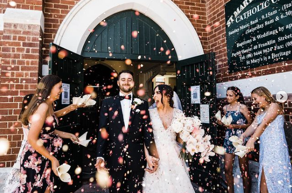 floral confetti being thrown on newlyweds outside of church wedding ceremony