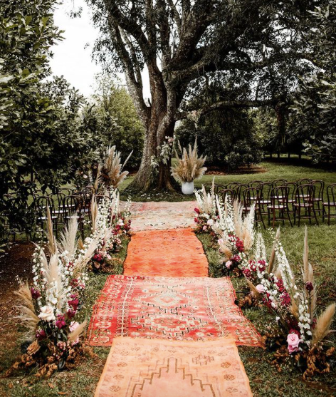 multicolored rugs as a wedding aisle runner for grass wedding