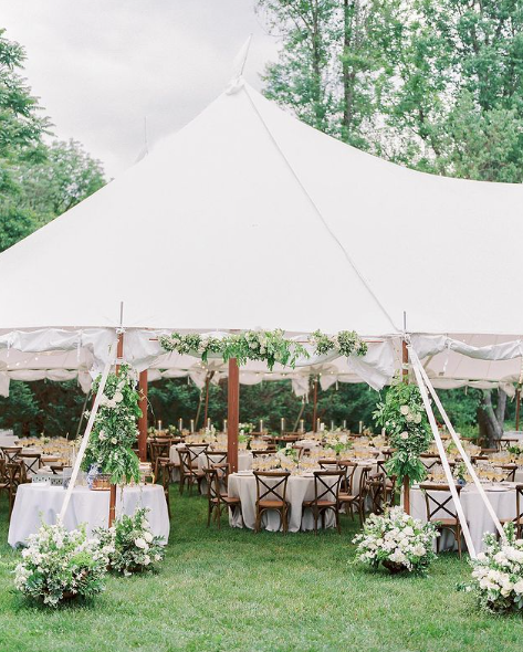 outdoor tent wedding reception with white linens and cross back chairs