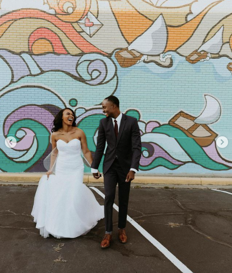 bride and groom happily posing for outdoor photographs against a graffiti wall