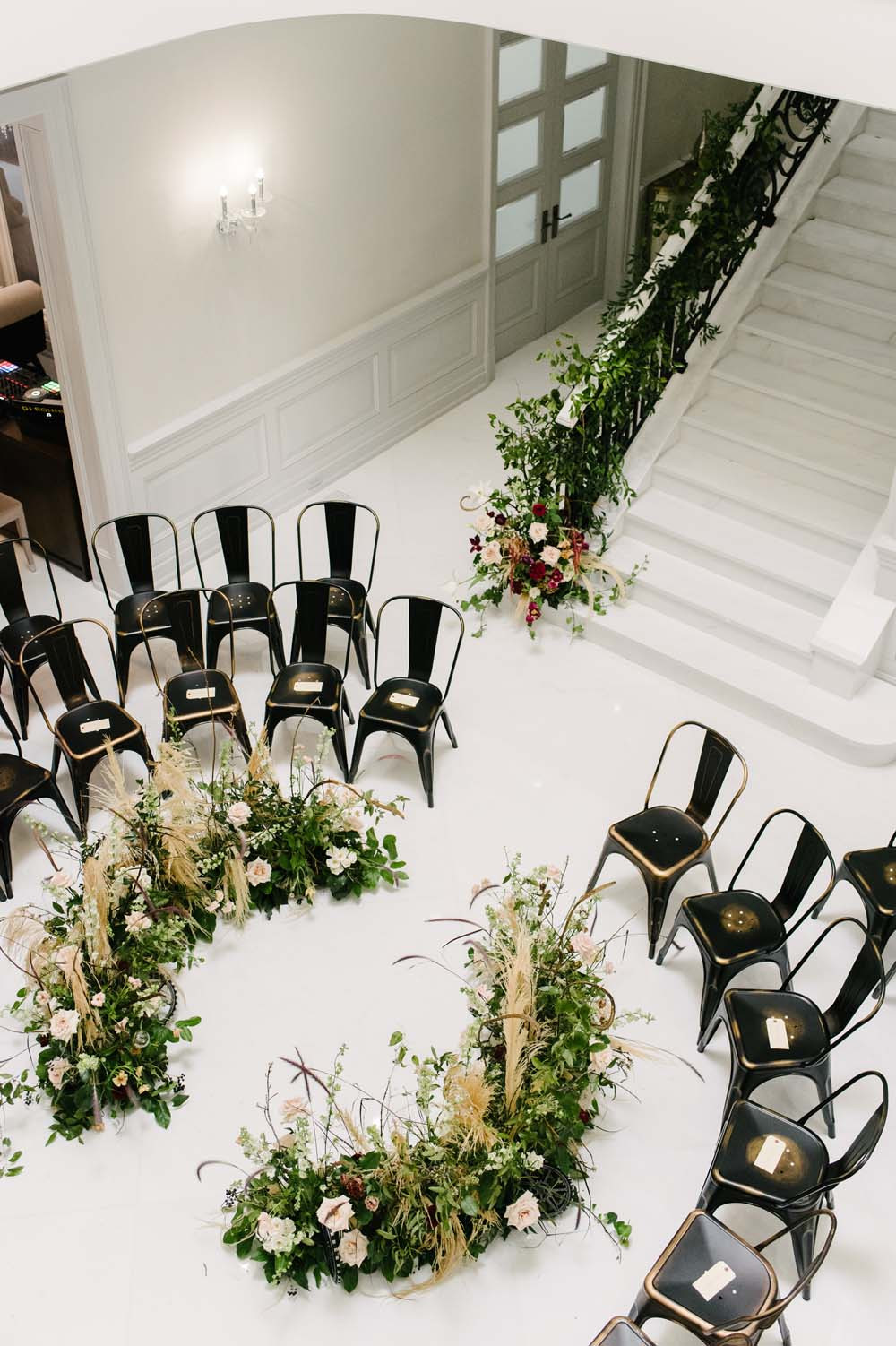 lobby wedding ceremony with marais chairs in a circle around floral altar