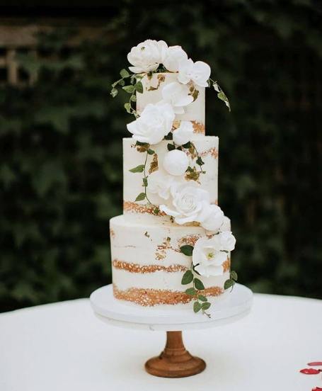 naked three-tier wedding cake on white and brown cake stand with florals