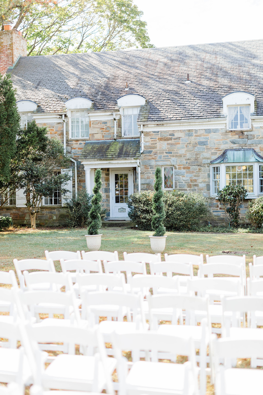 backyard wedding ceremony with white resin chairs