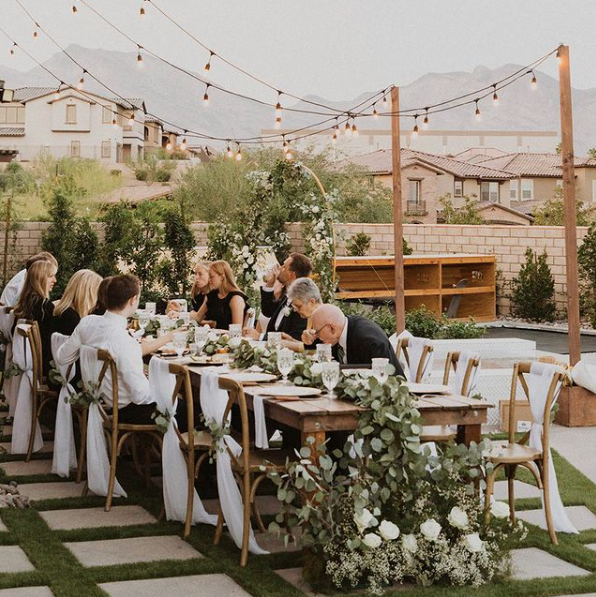 backyard wedding reception near pool under string lights