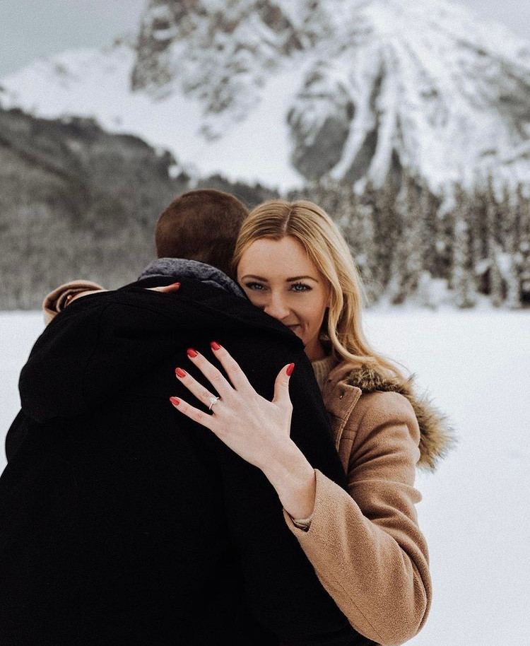 newly engaged couple hugging in snow capped mountains