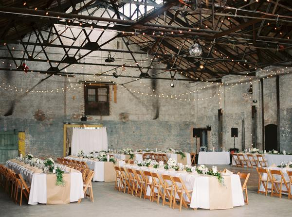 wedding reception with rectangular tables and string lights in a warehouse