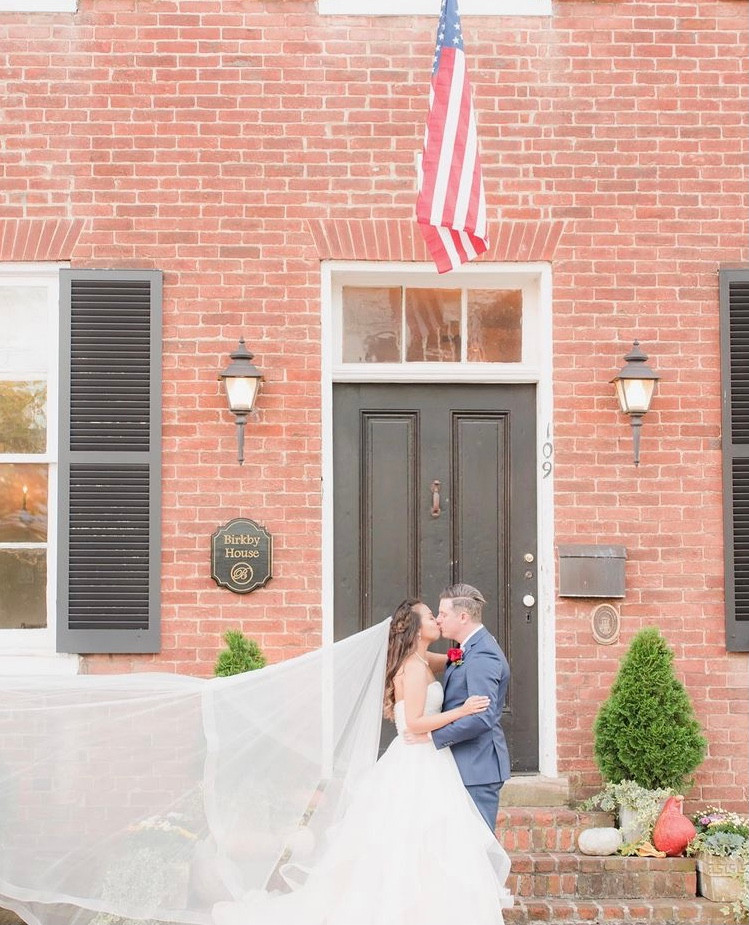 bride and groom kissing under American flag at Birkby House