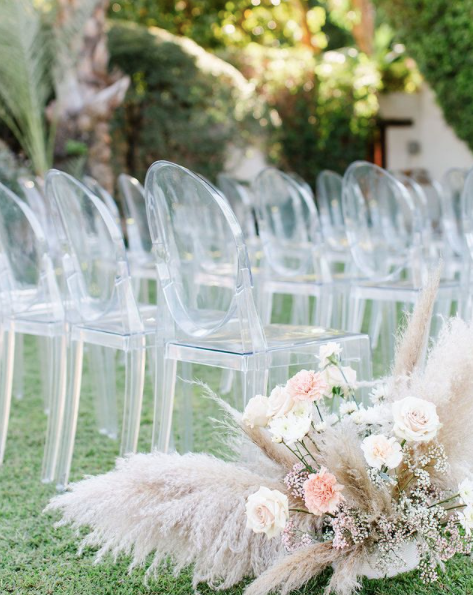 Outdoor wedding ceremony with ghost chairs and pampas grass