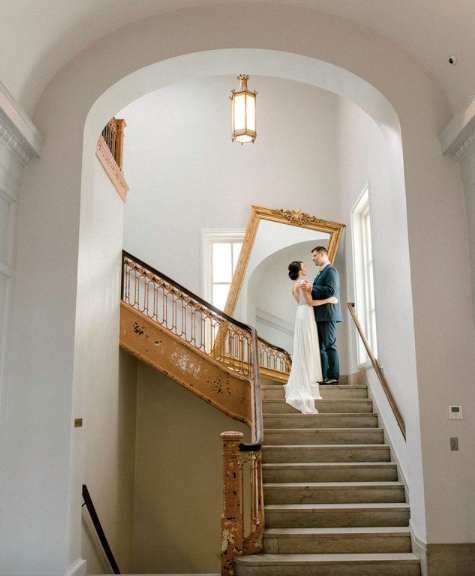 bride and groom first look posing on the stairs of a wedding venue