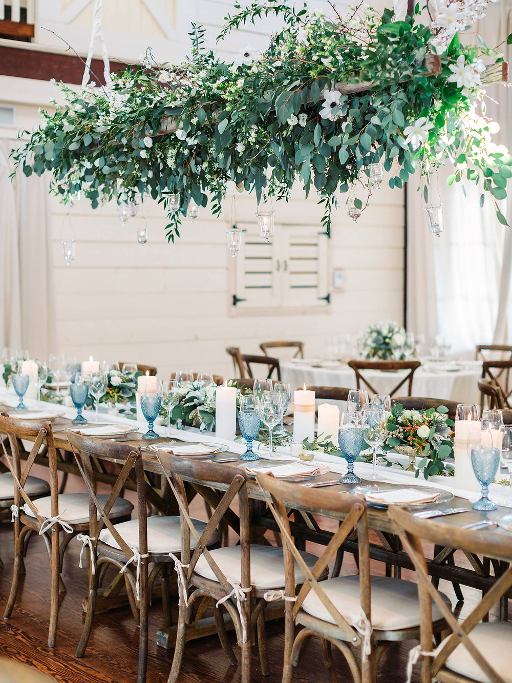 hanging greenery over wood wedding reception table with cross back chairs and blue water goblets