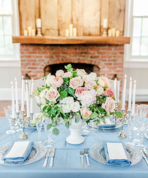 light blue tablecloth with pastel flowers and white candlesticks in front of fireplace