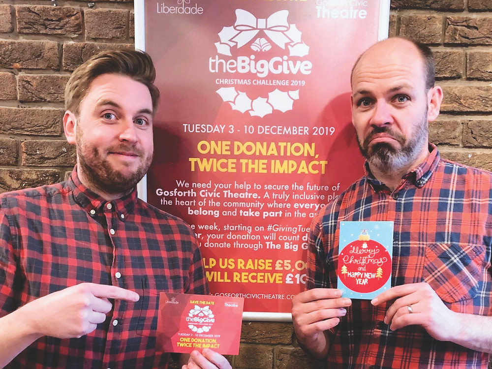 Scott and Liberdade CEO, Rob, posing with a postcard and Christmas Card in front of a poster for our Big Give campaign in 2019