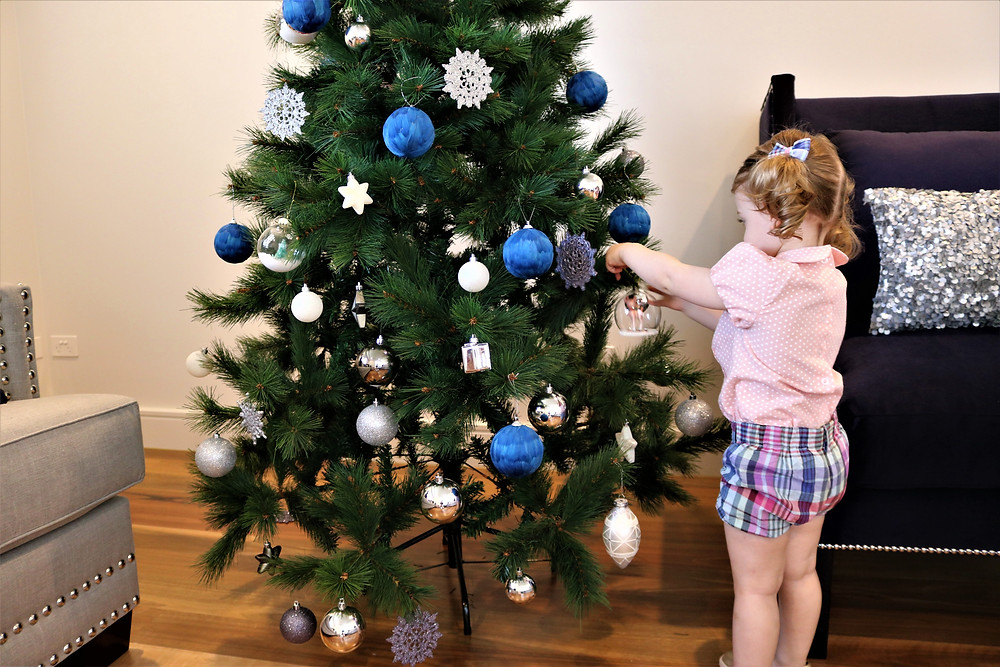 Little Miss putting decorations on the Christmas tree