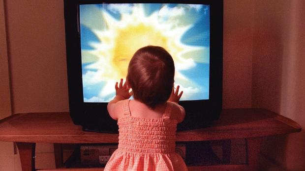 Toddler touching TV screen