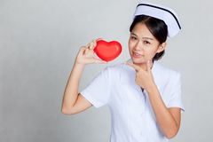 young-asian-nurse-point-to-red-heart-gray-background-44239284 (1)