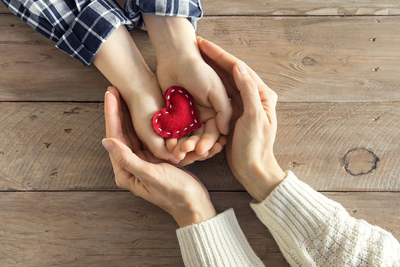 Red heart in child and female hands over