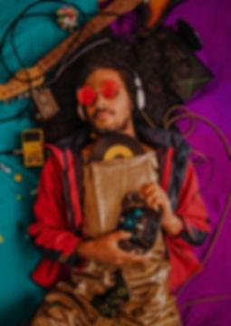 beard-man-holding-cassette-lying-on-blue